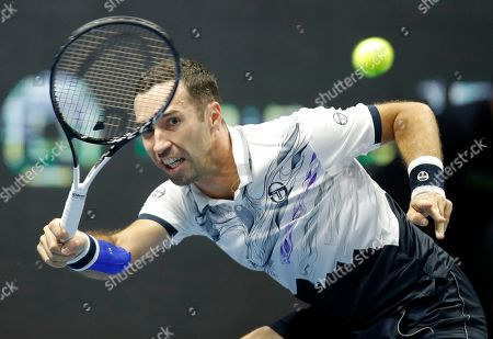 Mikhail Kukushkin of Kazakhstan returns the ball to Damir Dzumhur of Bosnia and Herzegovina during the St. Petersburg Open ATP tennis tournament match in St.Petersburg, Russia