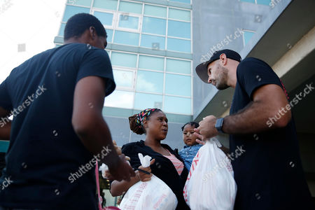 """Nick Mills, Leshonda Collins. Volunteer Nick Mills, right, hands Hurricane Dorian evacuee, Leshonda Collins and her 1-year-old daughter Shayniyah, supplies as they arrive from the Grand Celebration cruise ship from Freeport, a city in the Grand Bahamas on in Riviera Beach. The cruise ship transported hundreds of evacuees seeking passage from Freeport after the damaged caused by Hurricane Dorian. """"I'm happy to be in the U.S., I'm going to work, work, work, and try to get a job,"""" says Collins"""