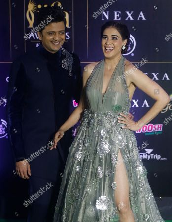 Stock Photo of Ritesh Deshmukh, Genelia Dsouza. Bollywood actor Ritesh Deshmukh stands with his wife Genelia Dsouza as they arrive to attend the 20th International Indian Film Academy (IIFA) awards ceremony in Mumbai, India