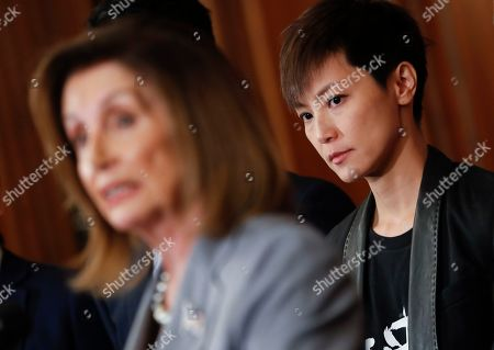 Stock Image of Nancy Pelosi, Joshua Wong, Denise Ho, Nathan Law. Hong Kong activist Denise Ho, right, listens to House Speaker Nancy Pelosi of Calif., left, speak during a news conference on human rights in Hong Kong on Capitol Hill in Washington