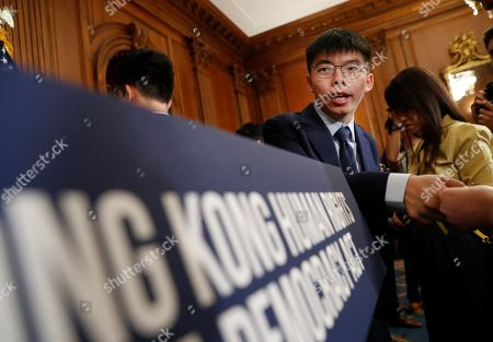 Nancy Pelosi, Joshua Wong, Denise Ho, Nathan Law. Hong Kong activist Joshua Wong, hands out his business card following a news conference on human rights in Hong Kong on Capitol Hill in Washington