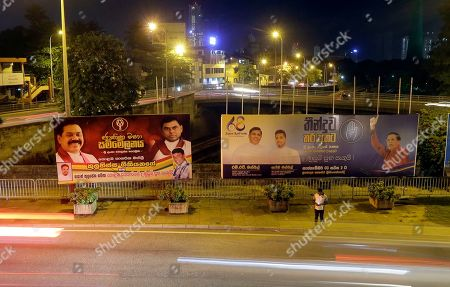 A Sri Lankan man stands near billboards displaying President Maithripala Sirisena, right, and former president Mahinda Rajapaksa, left, in Colombo, Sri Lanka, . Sri Lanka will hold a presidential election on Nov. 16, the elections office said Wednesday, amid calls for a strong leader to boost national security as the country recovers from deadly Easter Sunday bomb attacks