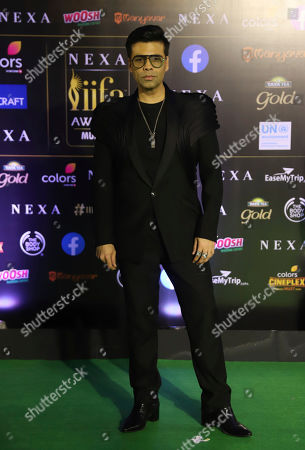 India filmmaker Karan Johar stands for photographs as he arrives to attend the 20th International Indian Film Academy (IIFA) awards ceremony in Mumbai, India