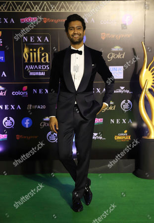 Indian actor Vicky Kaushal stands for photographs as he arrives to attend the 20th International Indian Film Academy (IIFA) awards ceremony in Mumbai, India