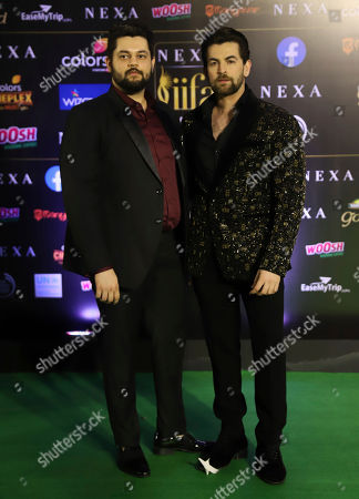Indian actor Neil Nitin Mukesh, right, stands for photographs as he arrives to attend the 20th International Indian Film Academy (IIFA) awards ceremony in Mumbai, India