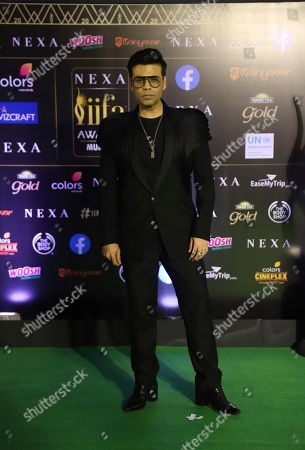 Stock Photo of India filmmaker Karan Johar stands for photographs as he arrives to attend the 20th International Indian Film Academy (IIFA) awards ceremony in Mumbai, India