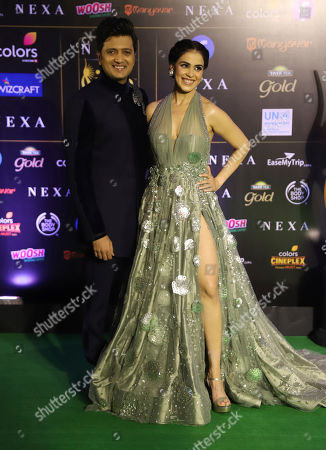 Bollywood actor Ritesh Deshmukh stands with his wife Genelia Dsouza for photographs as they arrive to attend the 20th International Indian Film Academy (IIFA) awards ceremony in Mumbai, India