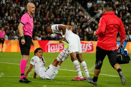 PSG's Marquinhos, second left, receives treatment from his teammate PSG's Presnel Kimpembe as he lies injured on the pitch during the Champions League group A soccer match between PSG and Real Madrid at the Parc des Princes stadium in Paris
