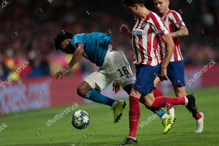 Atletico Madrid's Jose Gimenez, right, and Juventus' Juan Cuadrado, left, vie for the ball during the Champions League Group D soccer match between Atletico Madrid and Juventus at the Wanda Metropolitano stadium in Madrid, Spain