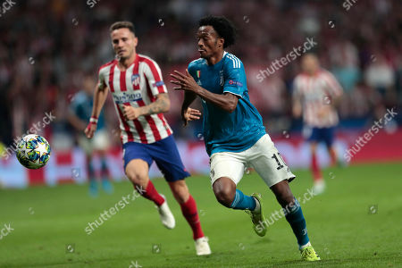 Atletico Madrid's Saul, left, and Juventus' Juan Cuadrado vie for the ball during the Champions League Group D soccer match between Atletico Madrid and Juventus at the Wanda Metropolitano stadium in Madrid, Spain