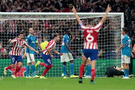 Atletico Madrid's Hector Herrera, center, and Atletico Madrid's Stefan Savic, left, celebrate after Herrara scored his side's second goal leaving Juventus' goalkeeper Wojciech Szczesny defeated on the ground, second right, during the Champions League Group D soccer match between Atletico Madrid and Juventus at the Wanda Metropolitano stadium in Madrid, Spain