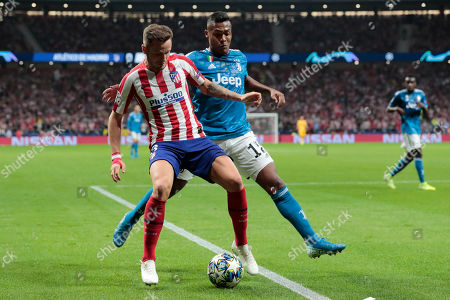 Juventus' Alex Sandro, right, and Atletico Madrid's Saul vie for the ball during the Champions League Group D soccer match between Atletico Madrid and Juventus at the Wanda Metropolitano stadium in Madrid, Spain
