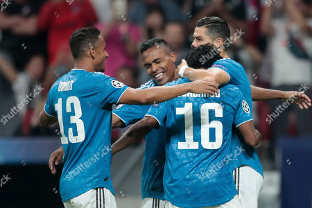 Juventus players hug teammate Juan Cuadrado, with number 16, after he scored his side's first goal during the Champions League Group D soccer match between Atletico Madrid and Juventus at the Wanda Metropolitano stadium in Madrid, Spain