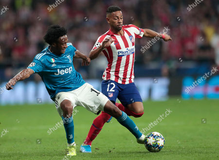 Juventus' Juan Cuadrado, left, and Atletico Madrid's Renan Lodi during the Champions League Group D soccer match between Atletico Madrid and Juventus at the Wanda Metropolitano stadium in Madrid, Spain