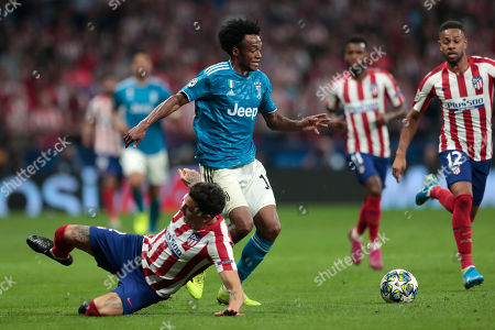 Juventus' Juan Cuadrado, center, vies for the ball with Atletico Madrid's Jose Gimenez, left, and Atletico Madrid's Renan Lodi, right, during the Champions League Group D soccer match between Atletico Madrid and Juventus at the Wanda Metropolitano stadium in Madrid, Spain