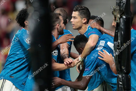 Juventus' Cristiano Ronaldo, center top, and other players hug teammate Blaise Matuidi, center low, after he scored his side's second goal during the Champions League Group D soccer match between Atletico Madrid and Juventus at the Wanda Metropolitano stadium in Madrid, Spain