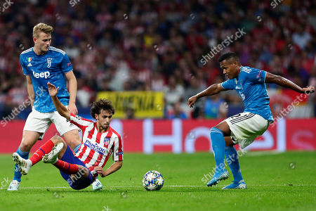 Atletico Madrid's Joao Felix fights for the ball against Juventus' Matthijs de Ligt, left, and Juventus' Alex Sandro, right, during the Champions League Group D soccer match between Atletico Madrid and Juventus at Wanda Metropolitano stadium in Madrid, Spain