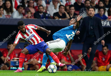 Juventus' Juan Cuadrado fights for the ball against Atletico Madrid's Thomas Lemar during the Champions League Group D soccer match between Atletico Madrid and Juventus at Wanda Metropolitano stadium in Madrid, Spain