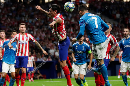 Juventus' Cristiano Ronaldo fights for the ball against Atletico Madrid's Stefan Savic during the Champions League Group D soccer match between Atletico Madrid and Juventus at Wanda Metropolitano stadium in Madrid, Spain