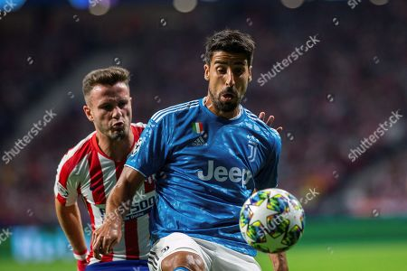 Atletico's midfielder Saul Niguez (L) in action against Juventus' midfielder Sami Khedira (R) during the UEFA Champions League group D soccer match between Atletico de Madrid and Juventus at Wanda Metropolitano stadium in Madrid, Spain, 18 September 2019.
