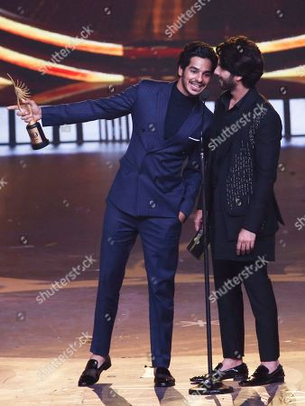 Stock Picture of Ishaan Khatter, Shahid Kapoor. Bollywood actor Ishaan Khatter, left, speaks with his half-brother Shahid Kapoor after he receives the award for Best Debut male actor role during the 20th International Indian Film Academy (IIFA) awards ceremony in Mumbai, India