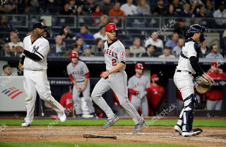 Los Angeles Angels shortstop Andrelton Simmons (C) scores between New York Yankees starting pitcher CC Sabathia (L) and teammate New York Yankees catcher Kyle Higashioka (R) on a hit by teammate Los Angeles Angels catcher Kevan Smith's RBI single to center field in third inning of play against the New York Yankees during their MLB game between the Los Angeles Angels and the New York Yankees at Yankee Stadium in the Bronx, New York, USA, 18 September 2019.