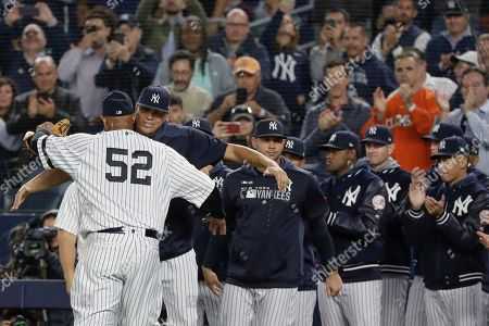 New York Yankees starting pitcher CC Sabathia, left, hugs relief pitcher Dellin Betances while teammates watch as he leaves during the third inning of the team's baseball game against the Los Angeles Angels, in New York