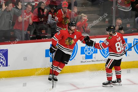 Chicago Blackhawks' Duncan Keith (2) celebrates with Patrick Kane (88) after scoring a goal during the second period of the team's preseason NHL hockey game against the Detroit Red Wings, in Chicago