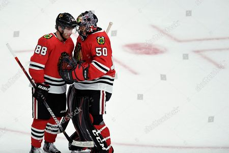 Chicago Blackhawks goalie Corey Crawford (50) celebrates with Patrick Kane (88) after the Blackhawks defeated the Detroit Red Wings in a preseason NHL hockey game, in Chicago
