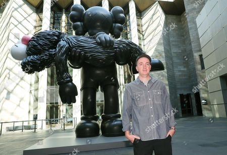 American artist Brian Donnelly, also known as KAWS, poses for photographs with his seven-meter tall bronze sculpture entitled 'GONE' is displayed during the 'KAWS: Companionship in the Age of Loneliness' exhibition at the National Gallery of Victoria in Melbourne, Australia, 19 September 2019.