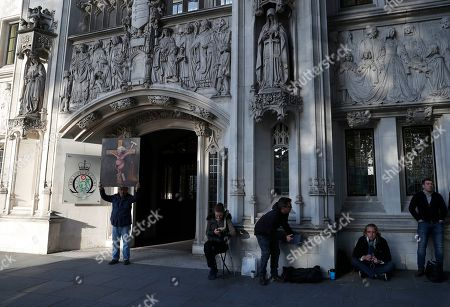 Satirical artist Kaya Mar poses for the media with his latest politically inspired painting outside The Supreme Court in London, . The Supreme Court is set to decide whether Prime Minister Boris Johnson broke the law when he suspended Parliament on Sept. 9, sending lawmakers home until Oct. 14 ? just over two weeks before the U.K. is due to leave the European Union