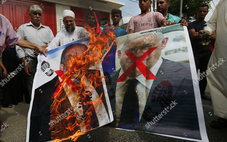 Palestinian supporters of the Democratic Front for the Liberation of Palestine (DFLP) burn pictures depicting Israeli Prime Minister Benjamin Netanyahu and Avigdor Lieberman, head of Yisrael Beitenu party, in solidarity with prisoners from Israeli jails, in Khan Younis in the southern Gaza Strip