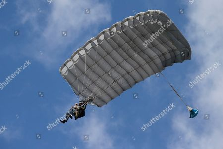 Tom Rice, a 98-year-old American WWII veteran, front left, approaches the landing zone during a tandem parachute jump near Groesbeek, Netherlands, as part of commemorations marking the 75th anniversary of Operation Market Garden. Rice jumped with the U.S. Army's 101st Airborne Division in Normandy, landing safely despite catching himself on the exit and a bullet striking his parachute