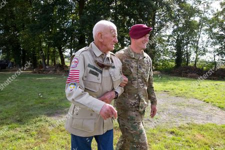 Tom Rice, a 98-year-old American WWII veteran, is escorted by a 101st Airborne Division officer after landing a tandem parachute jump from near Groesbeek, Netherlands, as part of commemorations marking the 75th anniversary of Operation Market Garden. Rice jumped with the U.S. Army's 101st Airborne Division in Normandy, landing safely despite catching himself on the exit and a bullet striking his parachute
