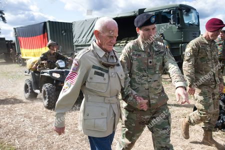Tom Rice, a 98-year-old American WWII veteran, is escorted by a 101st Airborne Division officers after landing a tandem parachute jump from near Groesbeek, Netherlands, as part of commemorations marking the 75th anniversary of Operation Market Garden. Rice jumped with the U.S. Army's 101st Airborne Division in Normandy, landing safely despite catching himself on the exit and a bullet striking his parachute
