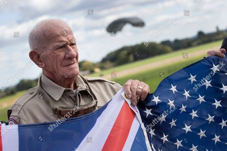 Tom Rice, a 98-year-old American WWII veteran, poses with the U.S. flag after landing with a tandem parachute jump near Groesbeek, Netherlands, as part of commemorations marking the 75th anniversary of Operation Market Garden. Rice jumped with the U.S. Army's 101st Airborne Division in Normandy, landing safely despite catching himself on the exit and a bullet striking his parachute