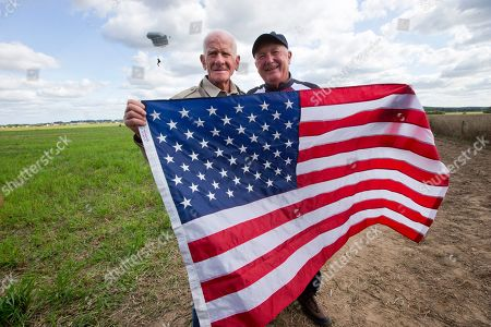 Tom Rice, a 98-year-old American WWII veteran, and U.S. Ambassador Pete Hoekstra, right, pose with the U.S. flag after landing with a tandem parachute jump from a plane near Groesbeek, Netherlands, as part of commemorations marking the 75th anniversary of Operation Market Garden. Rice jumped with the U.S. Army's 101st Airborne Division in Normandy, landing safely despite catching himself on the exit and a bullet striking his parachute