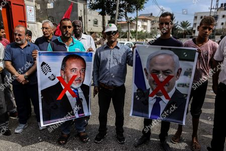 Palestinians hold portraits of Israeli Prime Minister Benjamin Netanyahu and Avigdor Lieberman head of Yisrael Beitenu party during the protest demanding the release of Palestinian prisoners from Israeli jails in southern Gaza.