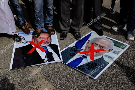 Palestinians step on portraits of Israeli Prime Minister Benjamin Netanyahu and Avigdor Lieberman head of Yisrael Beitenu party during the protest demanding the release of Palestinian prisoners from Israeli jails in southern Gaza.