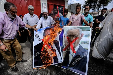 Palestinians burn a portrait of Avigdor Lieberman head of Yisrael Beitenu party during the protest demanding the release of Palestinian prisoners from Israeli jails in southern Gaza.