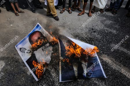 Palestinians burn portraits of Israeli Prime Minister Benjamin Netanyahu and Avigdor Lieberman head of Yisrael Beitenu party during the protest demanding the release of Palestinian prisoners from Israeli jails in southern Gaza.