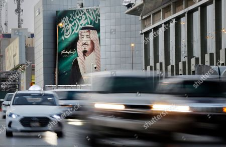 """In this picture taken with low shutter speed, vehicles passes in front of a banner showing Saudi King Salman, with Arabic that reads """"We pledge you to listen and obey"""" at a shopping mall, in Riyadh, Saudi Arabia, . Any attack on Iran by the U.S. or Saudi Arabia will spark an """"all-out war,"""" Tehran's top diplomat warned Thursday, raising the stakes as Washington and Riyadh weigh a response to a drone-and-missile strike on the kingdom's oil industry that shook global energy markets"""