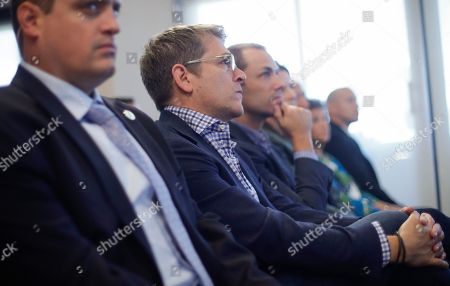 Jay Carney, center, Senior Vice President of Global Corporate Affairs at Amazon, sits in the front row as he listens to Amazon CEO Jeff Bezos speak during his news conference at the National Press Club in Washington, . Carney was the former White House press secretary to President Barack Obama and currently oversees public policy and public relations for all of Amazon's businesses around the world