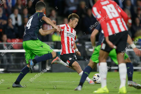PSV's Ritsu Doan of Japan, center, shoots on goal as Sporting's Sebastian Coates tries to block the shot during the Europa League Group D soccer match between PSV and Sporting CP at the Philips stadium in Eindhoven, Netherlands