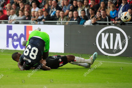 Sporting's Yannick Bolasie falls after a sliding by PSV's Denzel Dumfries during the Europa League Group D soccer match between PSV and Sporting CP at the Philips stadium in Eindhoven, Netherlands