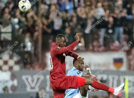 CFR's Lacina Traore, left, jumps for a header with Lazio's Bastos during the Europa League, group E, soccer match between CFR Cluj and Lazio at the Constantin Radulescu stadium in Cluj, Romania