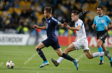 Malmo's Arnor Ingvi Traustason, left, and Dynamo Kyiv's Volodymyr Shepelyev challenge for the ball during the Europa League group B soccer match between Dynamo Kyiv and Malmo FF at the Olympiyskiy stadium in Kyiv, Ukraine