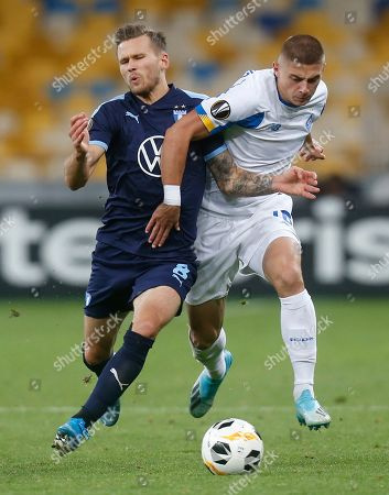 Malmo's Arnor Ingvi Traustason, left, and Dynamo Kyiv's Vitaliy Mykolenko challenge for the ball during the Europa League group B soccer match between Dynamo Kyiv and Malmo FF at the Olympiyskiy stadium in Kyiv, Ukraine