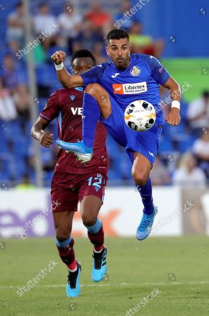 Stock Picture of Getafe's forward Angel Rodriguez (R) vies for the ball against Trabzonspor's midfielder John Obi Mikel (L) during the Europa League group C match between Getafe and Trabzonspor at Coliseum Alfonso Perez stadium in Getafe, Madrid, Spain, 19 September 2019.