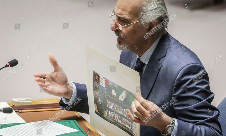 Stock Image of Syria's United Nations Ambassador Bashar Jaafari display pictures as he address a U.N. Security Council meeting on Syria, at U.N. headquarters